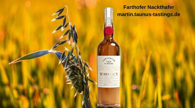 Eine Flasche Farthofer Nackthafer Whisky vor einem Haferfeld