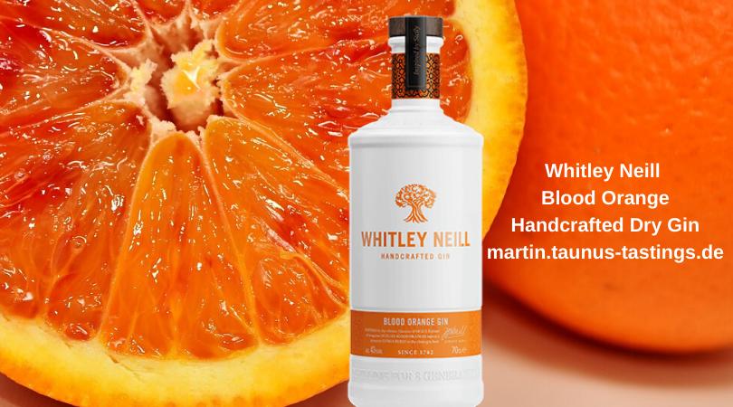 Eine Flasche Whitley Neill Blood Orange Handcrafted Dry Gin mit Blut Orangen im Hintergrund