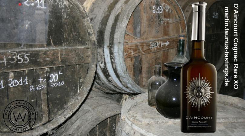 Eine Flasche D'Aincourt Cognac Rare XO mit alten Fässern im Hintergrund