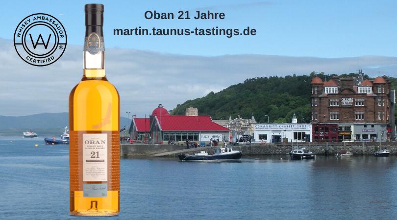 Eine Flasche Oban 21 Jahre mit der Bucht von Oban im Hintergrund