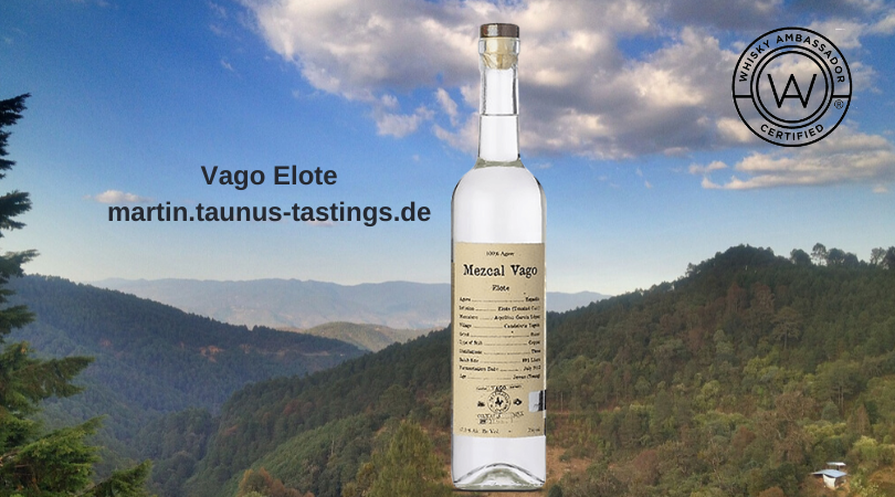 Eine Flasche Vago Elote mit den Bergen Oaxacas im Hintergrund