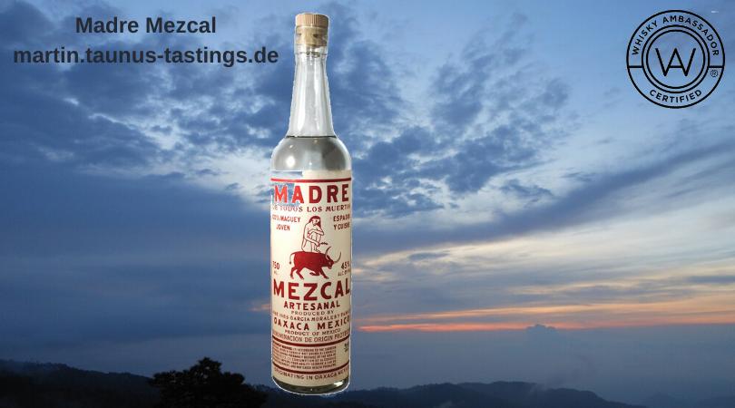 Eine Flasche Madre Mezcal mit dem Himmel von Oaxcaca im Hintergrund