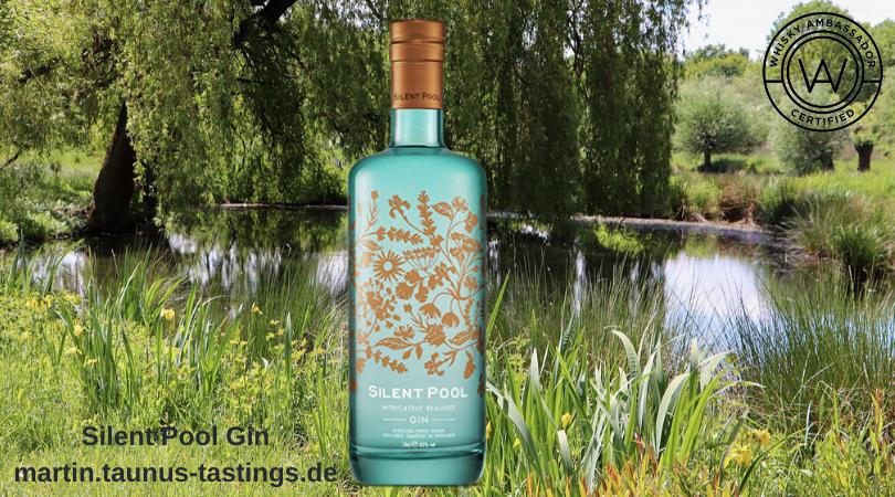 Eine Flasche Silent Pool Gin mit einem Teich im Hintergrund