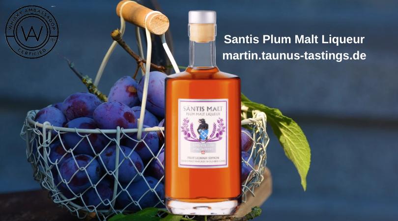 Eine Flasche Santis Plum Malt Liqueur mit einem Korb Pflaumen im Hintergrund
