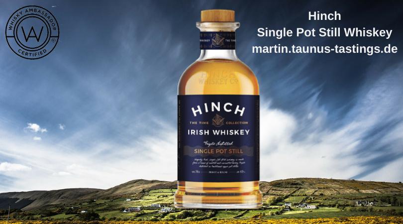 Eine Flasche Hinch Single Pot Still Irish Whiskey, im Hintergrund eine irische Landschaft