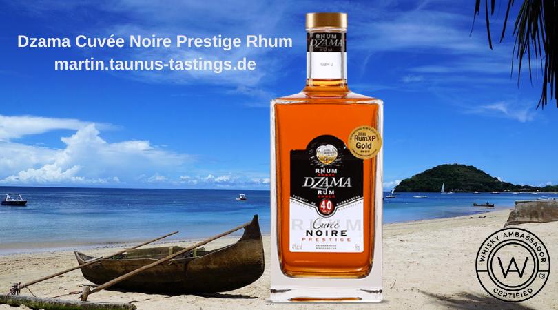 Eine Flasche Dzama Cuvée Noire Prestige Rhum, im Hintergrund ein Strand von Madagascar
