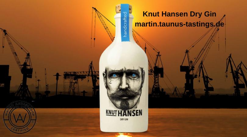 Eine Flsche Knut Hansen Dry Gin, im Hintergrund ein Pier in Hamburg im Sonnenuntergang